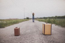 woman standing with her arms raised in the middle of a road in front of suitcases