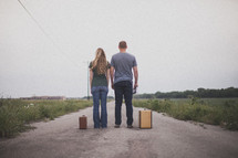 man and a woman standing in the middle of a road next to suitcases