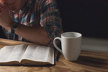 A man praying at a table with an open Bible and coffee cup.