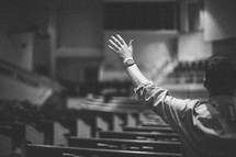 hands raised in worship to God inside an empty church