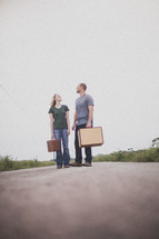 man and woman carrying luggage standing in the road