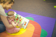 nursery staff and and infant reading a book