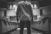 man standing in the aisle of an empty church