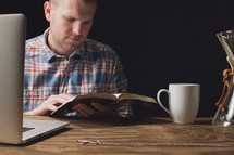Man reading the Bible while sitting at a wooden table with a laptop computer and a coffee cup.