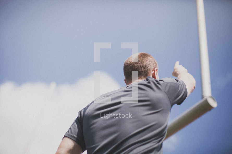 man pointing to a field goal post
