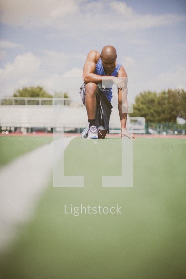 athlete kneeling in prayer on a football field