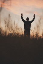 silhouette of a man with his hands raised in worship to God