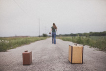 Woman with Bible in the middle of a dirt road, walking away from suitcases.