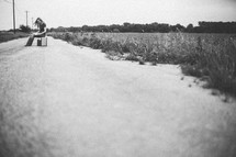 Woman sitting on a suitcase in the middle of a dirt road reading a bible.