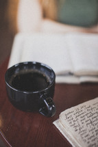 Coffee cup on a table with a Bible and notes.