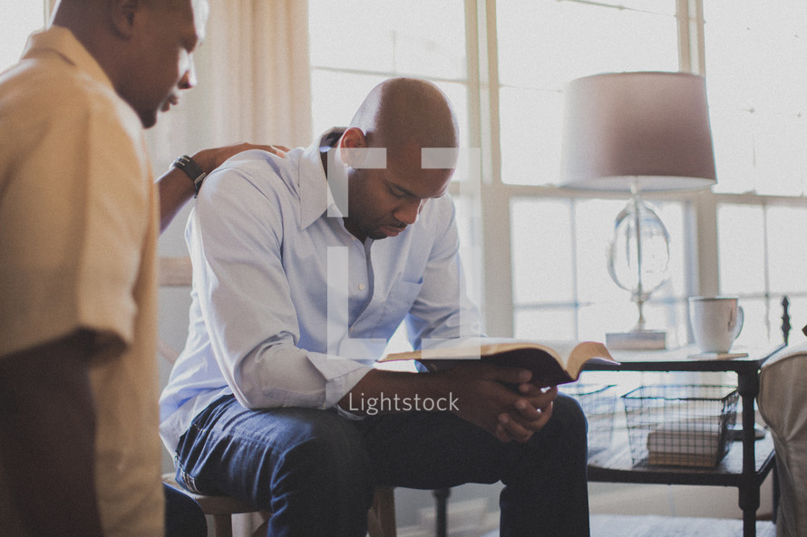 two men in prayer at a Bible study