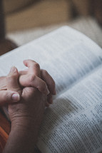 Hands clasped on an open Bible's pages.