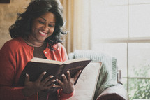 Joyful woman reading the Bible.