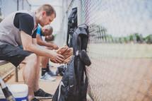 men praying in a baseball dugout