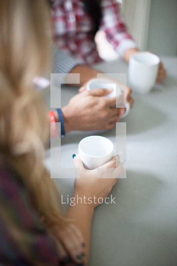 praying hands and coffee cups in hand