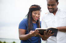 happy African-American couple reading a Bible together outdoors
