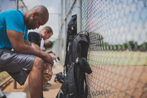 men praying in a baseball dugout