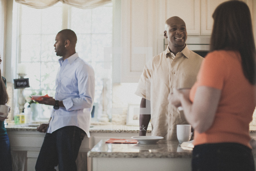 people in conversation in a kitchen at a Bible study