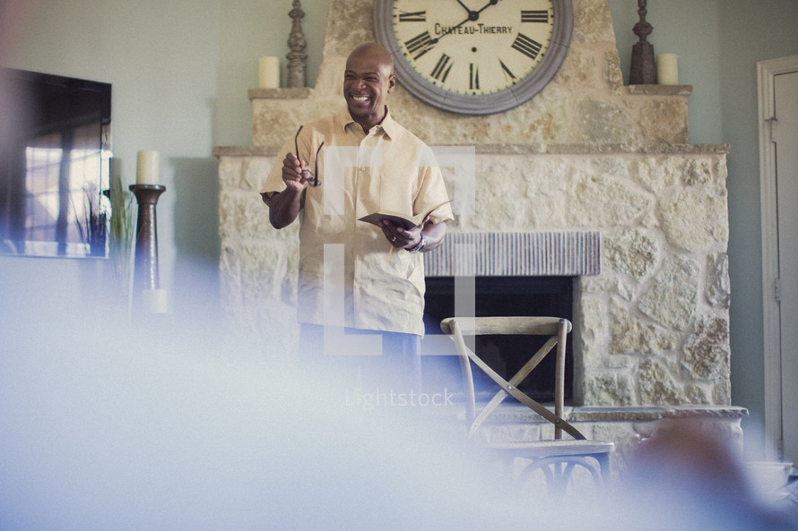man reading a Bible to others at a Bible study