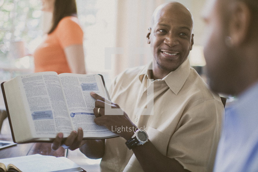 man pointing to scripture at a Bible study