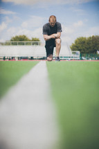 man kneeling in prayer on the football field