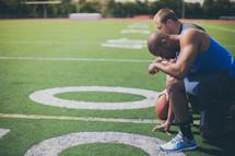 football players kneeling in prayer on the field