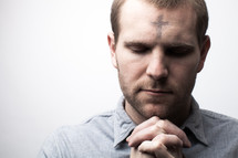 A man with ashes on his forehead in prayer for Ash Wednesday