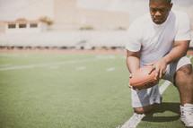 man in prayer on a football field