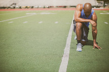 athlete kneeling in prayer on the football field