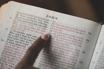 Finger pointing to John 3:16 in an open Bible.