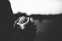 Hands holding a football.