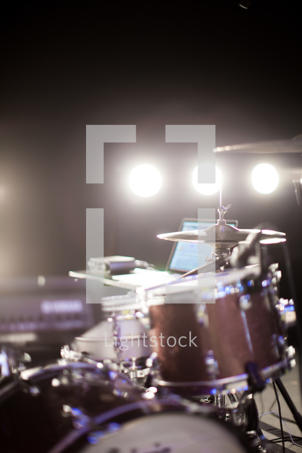 Drum set lit up with stage lighting.