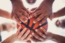 Players' hands holding a basketball.