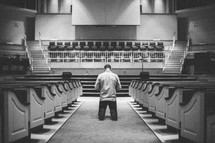 man kneeling in the aisle of a church in front of the altar