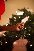 A woman touching an angel ornament on a Christmas tree