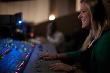 a woman behind a soundboard