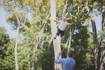 father tossing his son in the air