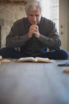 man reading a Bible and praying