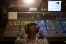 A man works with sound equipment in a sound booth.