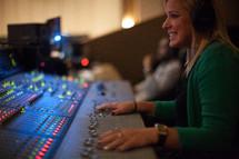 a woman at a soundboard
