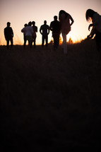 group of people walking outdoors at dusk