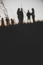 groups gathered outdoors talking in a field at sunset