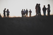 group gathered talking outdoors in a field at sunset