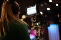a woman behind a video camera