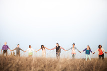 group holding hands in fellowship in a field