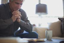 man praying over a Bible