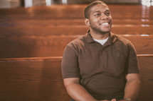 man sitting in a church looking up to God smiling