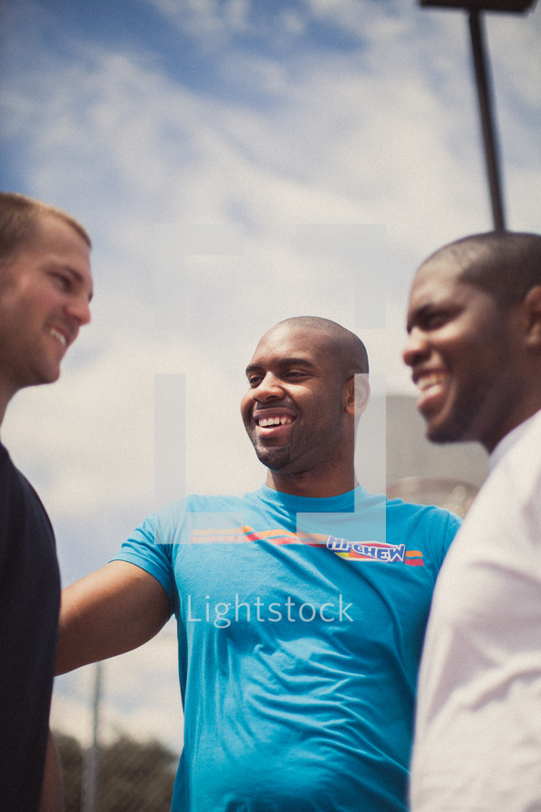 Three smiling men in a huddle.