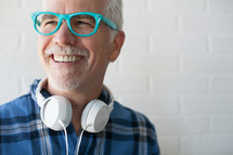 face of a man wearing reading glasses and headphones around his neck with a white beard