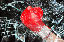 fist in a boxing glove breaking glass